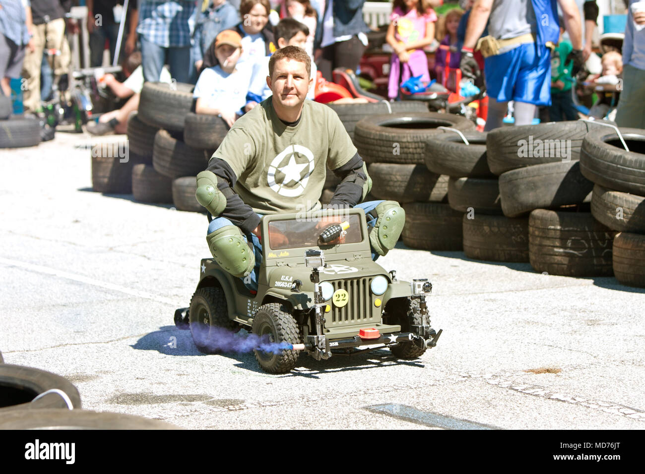 A man drives a miniature army jeep in the power racing series at the annual Maker Faire on October 4, 2014 in Decatur, GA. Stock Photo