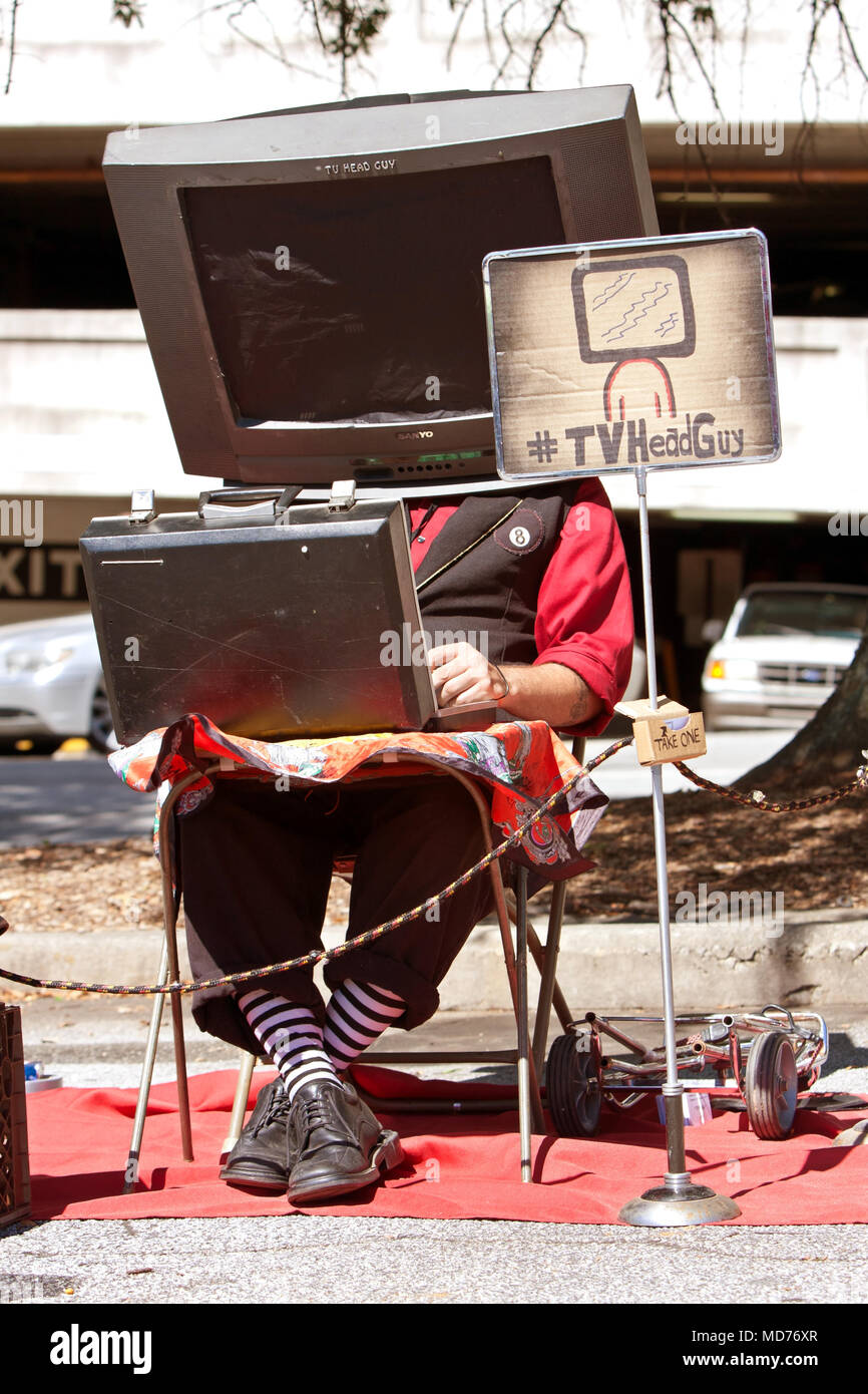 A man with a prop TV on his head, manipulates a circuit board to make the sounds of TV channels changing, on October 4, 2014 in Decatur, GA. - Stock Image