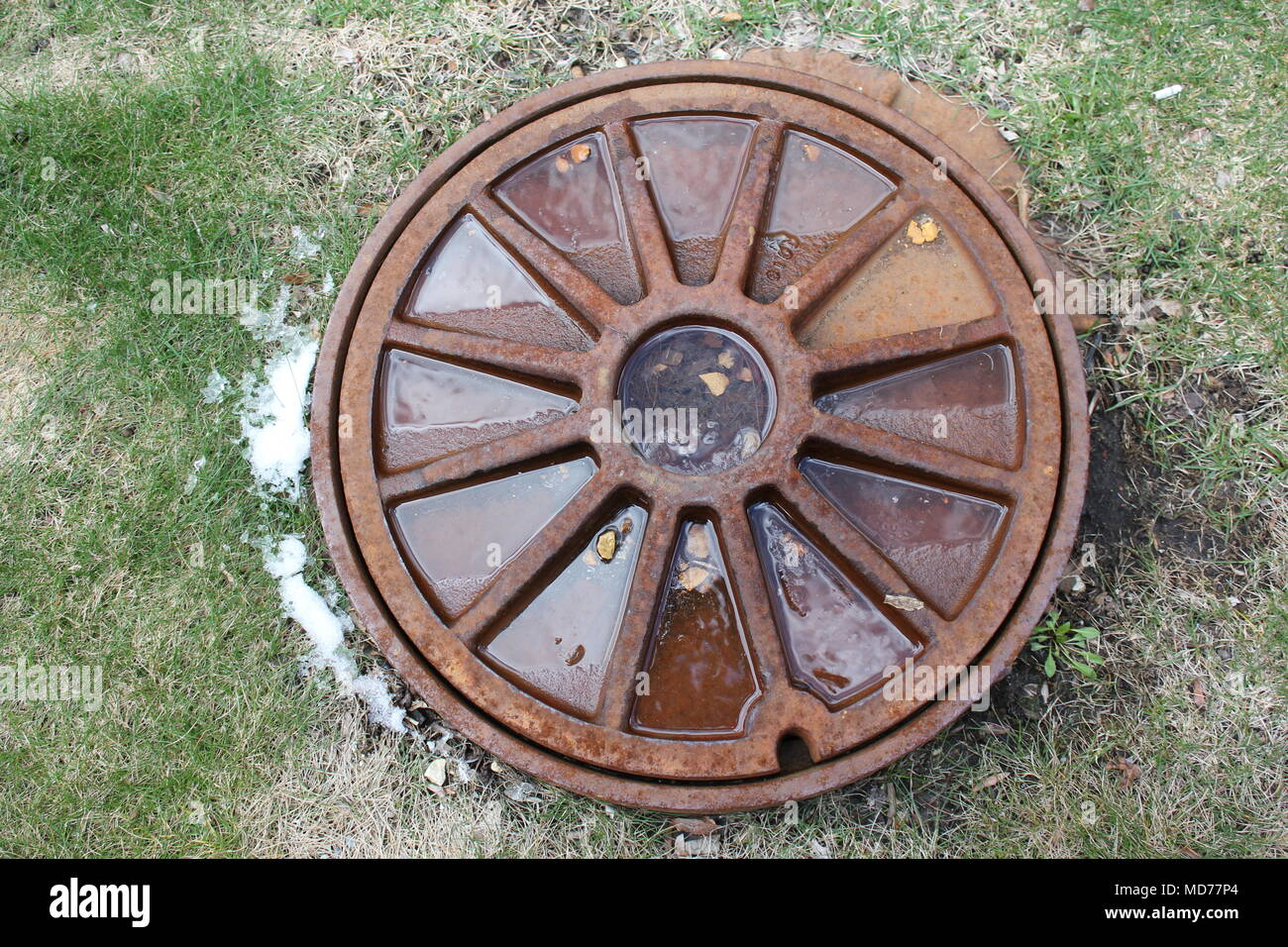 Decorative manhole cover for access to underground utilities. - Stock Image