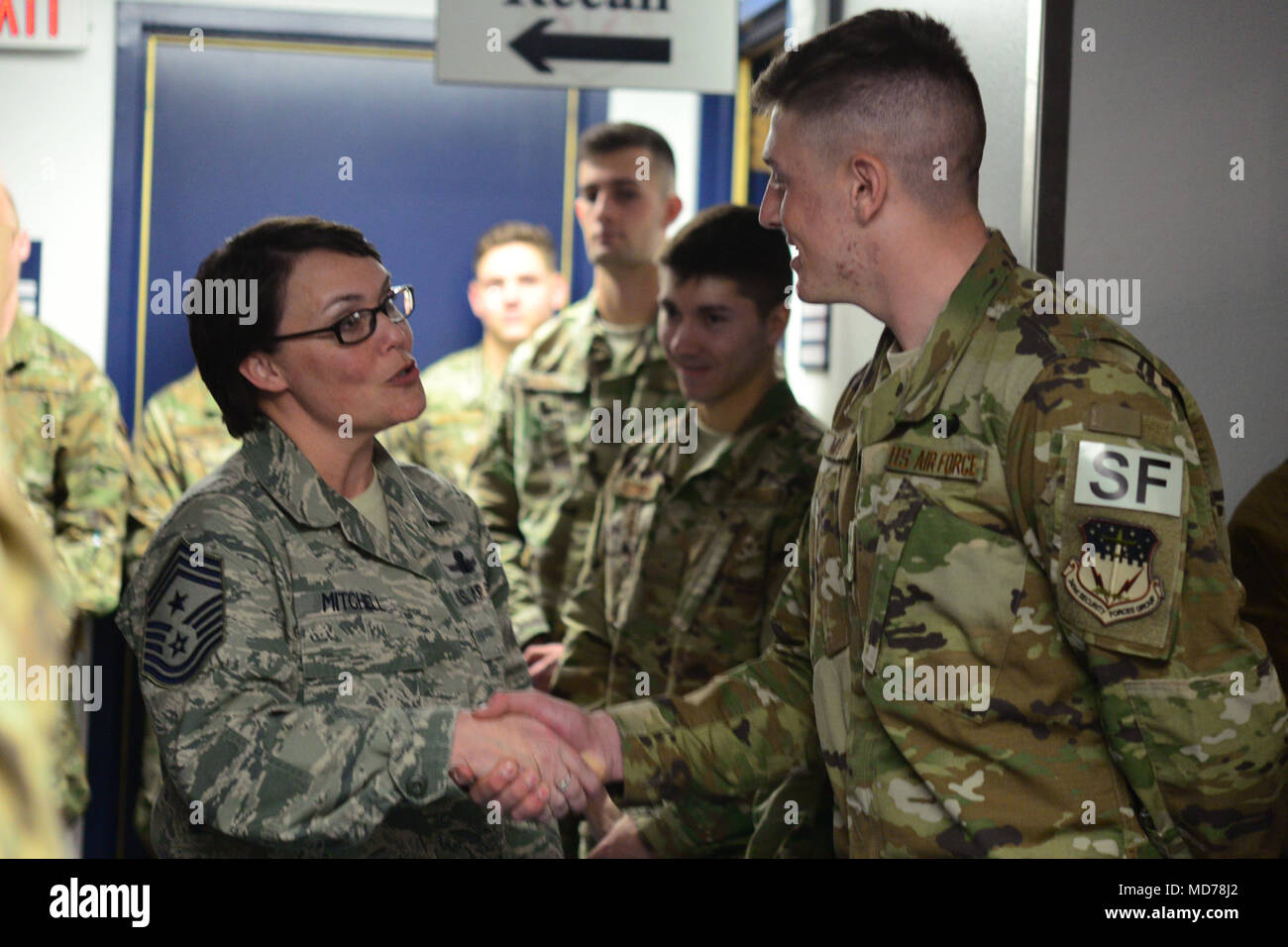 Chief Master Sgt. Amber Mitchell, 341st Missile Wing command chief, left, presents a coin to Airman Gideon Magrini, 841st Missile Security Forces Squadron missile security operator, Mar. 23, 2018, at Malmstrom Air Force Base, Mont. Magrini was among 117 graduates from the Air Assault School in Fort Bliss, Texas, in March. (U.S. Air Force photo by Airman 1st Class Tristan Truesdell) - Stock Image