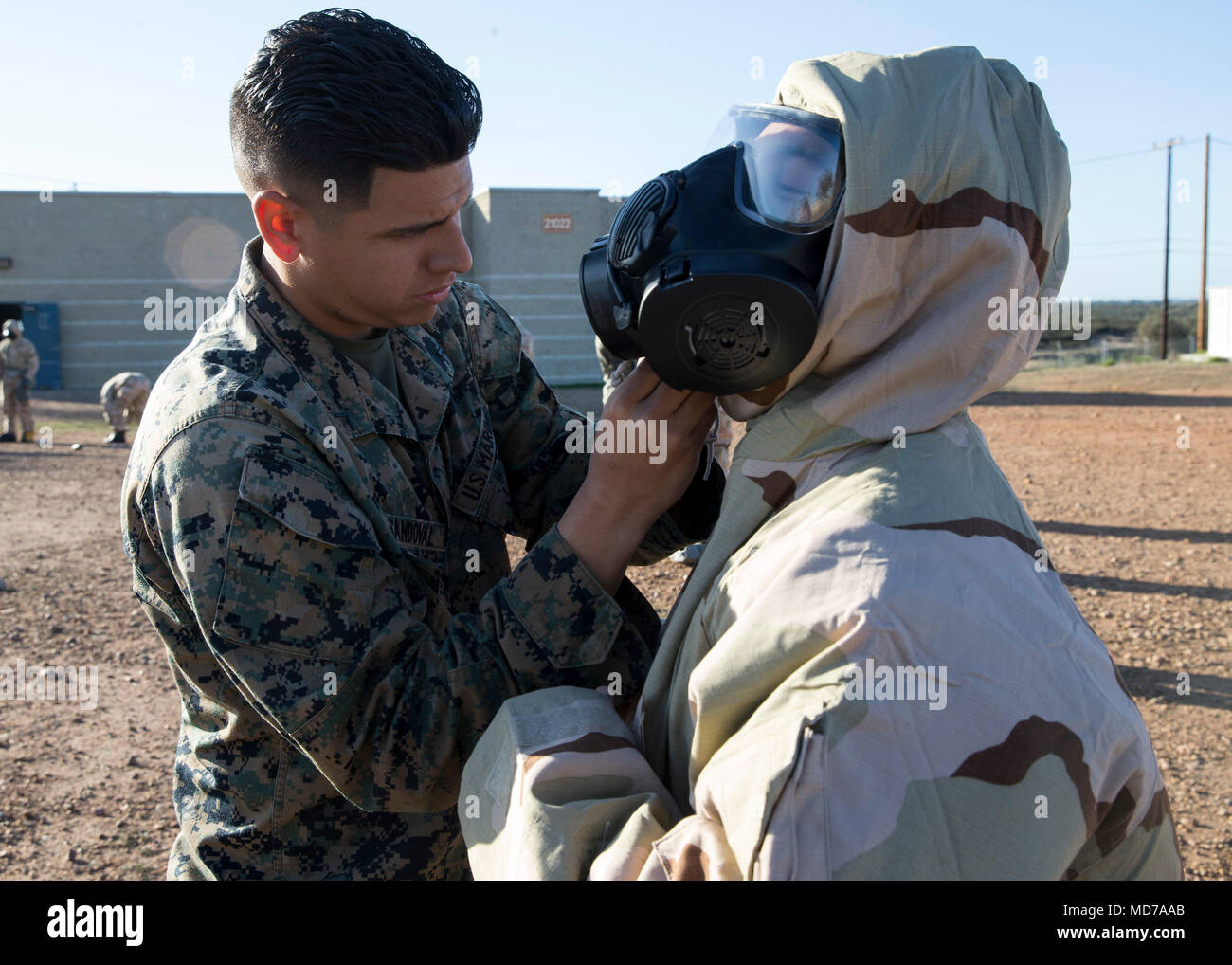 Pfc. Luis Sandoval, a cyber network operator with 3rd Marine Aircraft Wing, helps a Marine don a Mission Oriented Protective Posture suit during the reconnaissance, surveillance and decontamination course at Marine Corps Air Station Miramar, Calif., March 25. The course is designed to train unit personnel in the procedures and equipment used in accomplishing RS&D operations in a chemical, biological, radiological or nuclear environment. (U.S. Marine Corps photo by Lance Cpl. Clare J. McIntire) - Stock Image
