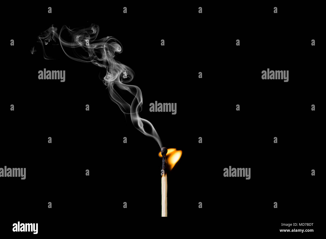Matchstick burning with little flame and smoke on black background - Stock Image