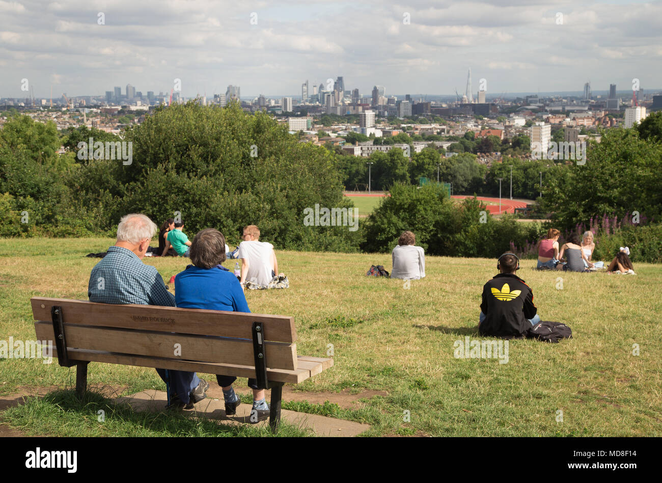 People relax and enjoy the panoramic view of the London skyline on a summer afternoon on Parliament Hill on Hampstead Heath in north London - Stock Image