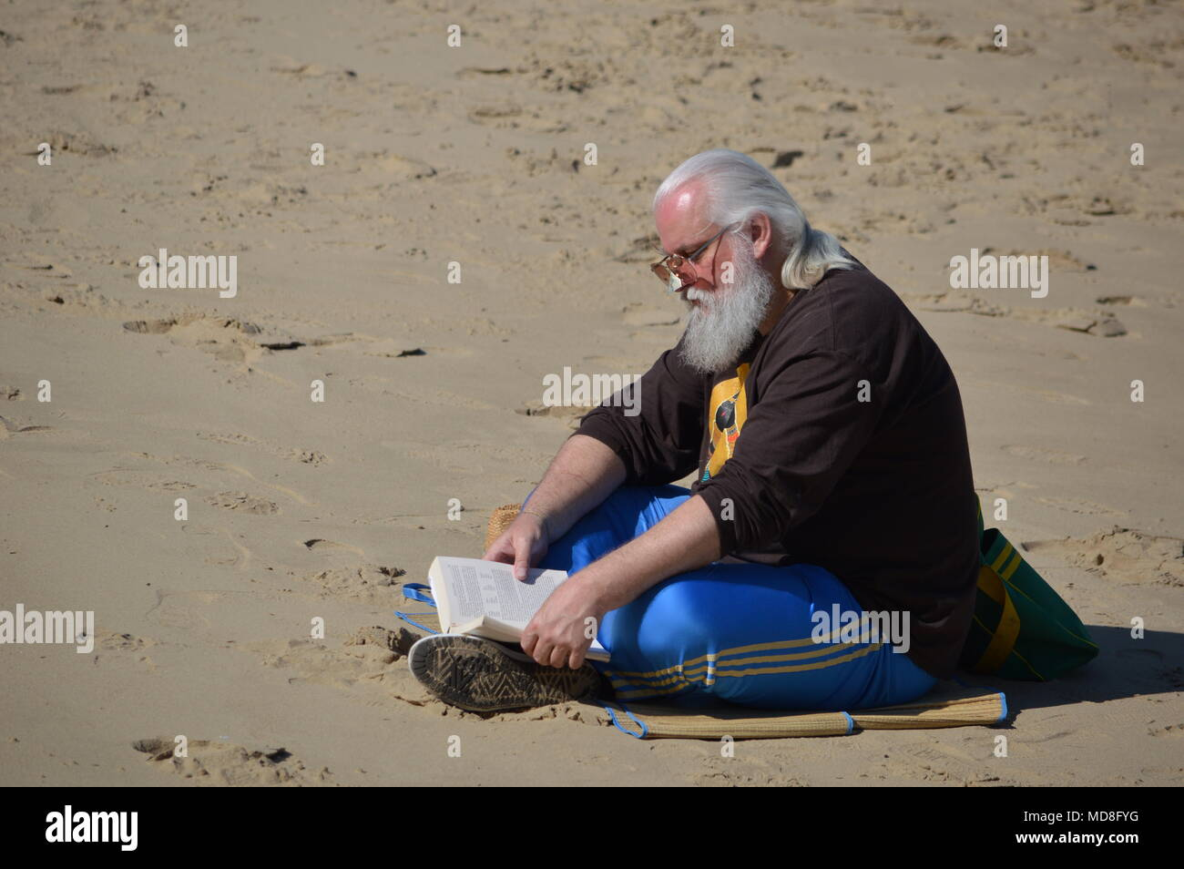 A man reading a book on the bank of the River Thames at Southbank, London - Stock Image