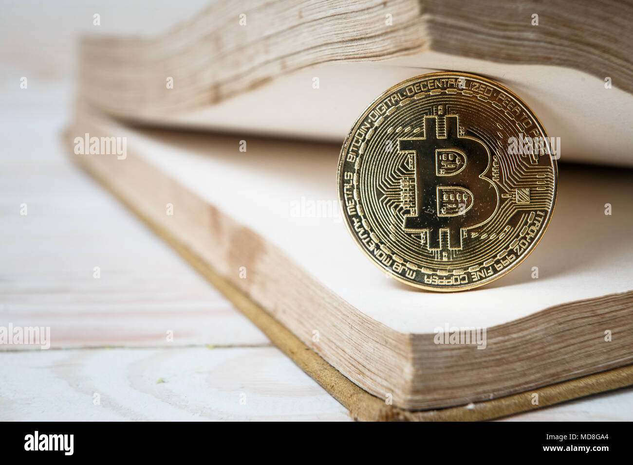 Golden bitcoin on open book electronic or digital money - Stock Image