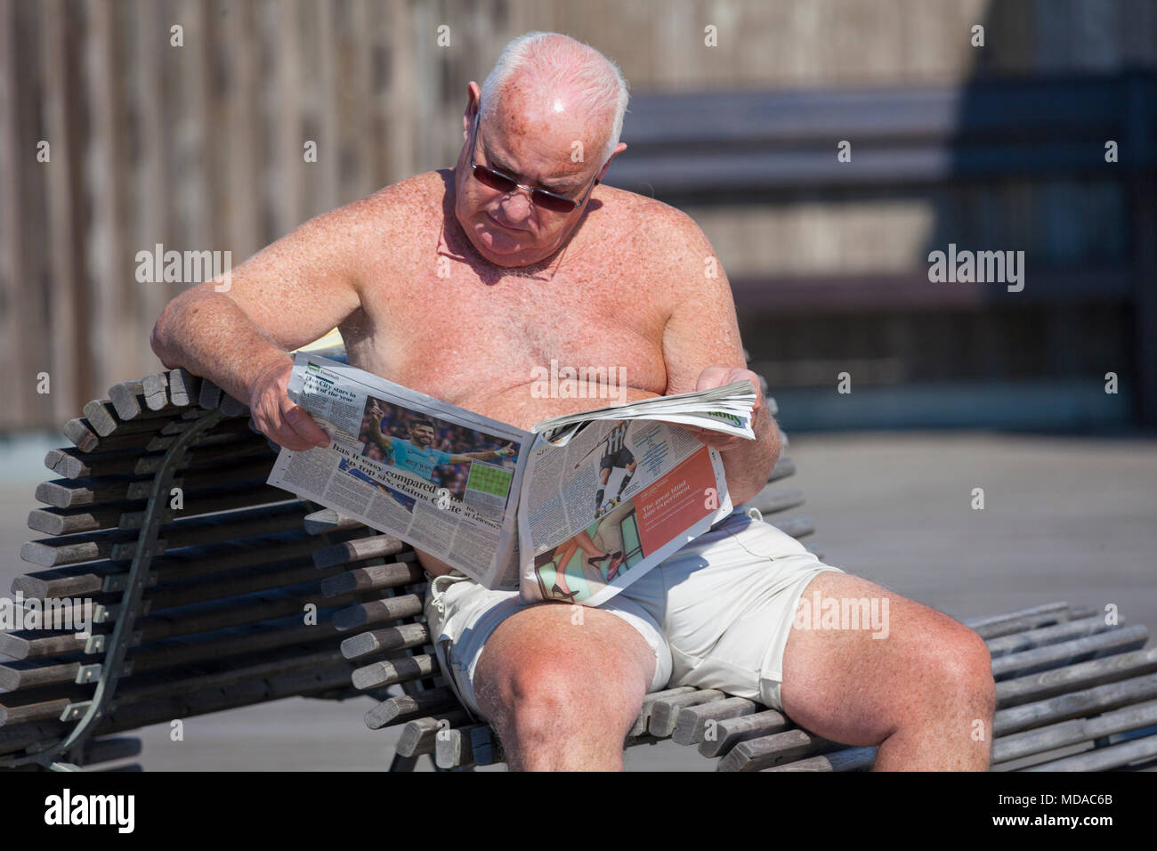 Hastings, East Sussex, UK. 19th Apr, 2018. UK Weather: A hot start to the day in the seaside town of Hastings on the South East coast with temperatures expected to exceed 23°C. Lots of people are out and about taking advantage of the mini heat wave that is hitting Britain. Man reads a newspaper while sunbathing sitting on a bench. © Paul Lawrenson 2018, Photo Credit: Paul Lawrenson / Alamy Live News - Stock Image