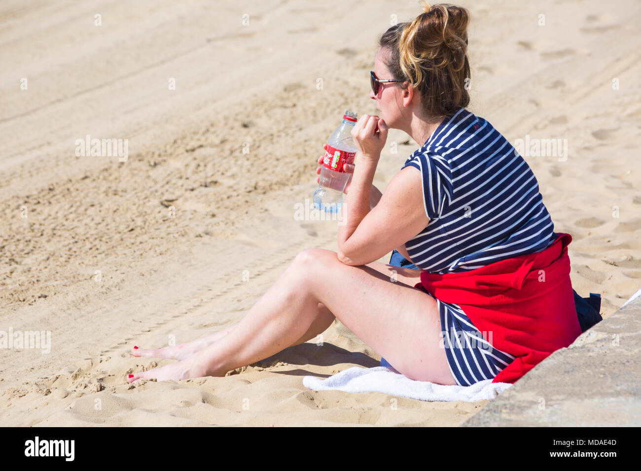 Bournemouth, Dorset, UK. 19th April 2018. UK weather: lovely warm sunny day at Bournemouth beaches with clear blue skies and unbroken sunshine, as visitors head to the seaside to enjoy the warmest day of the year so far. Young woman sitting on beach holding empty Coca-Cola bottle. Credit: Carolyn Jenkins/Alamy Live News Stock Photo