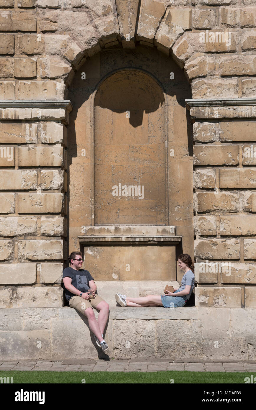 Oxford, UK. 19th April 2018. Oxford University students take a break from studies outside the world-famous Radcliffe Camera, part of the Bodleian Library. Today is predicted to be one of the hottest April days on record, at around 27°C. Credit: Martin Anderson/Alamy Live News. - Stock Image