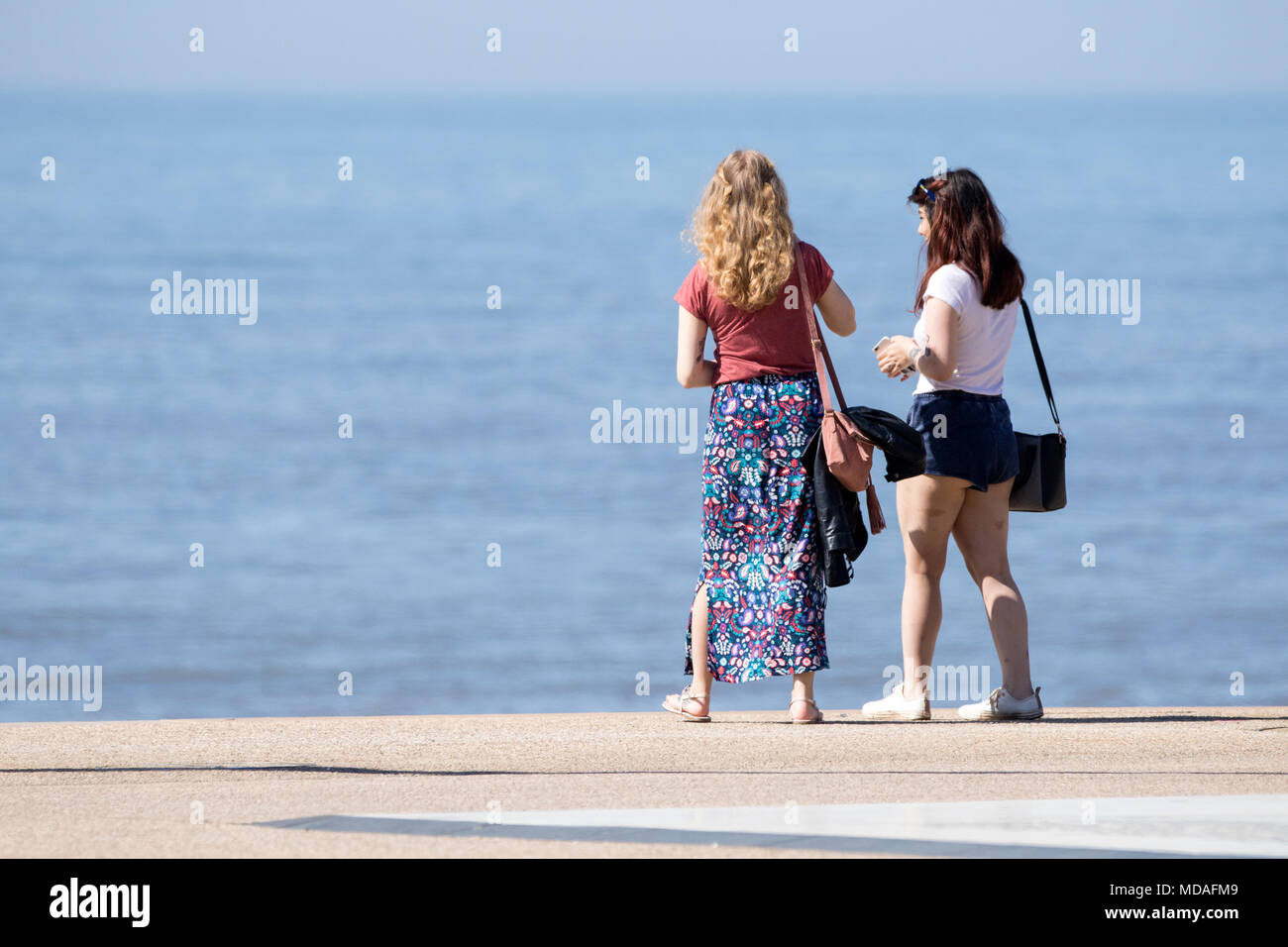 Two teenage girls stand and look at the tide coming in at the seaside resort town of Blackpool in Lancashire. - Stock Image
