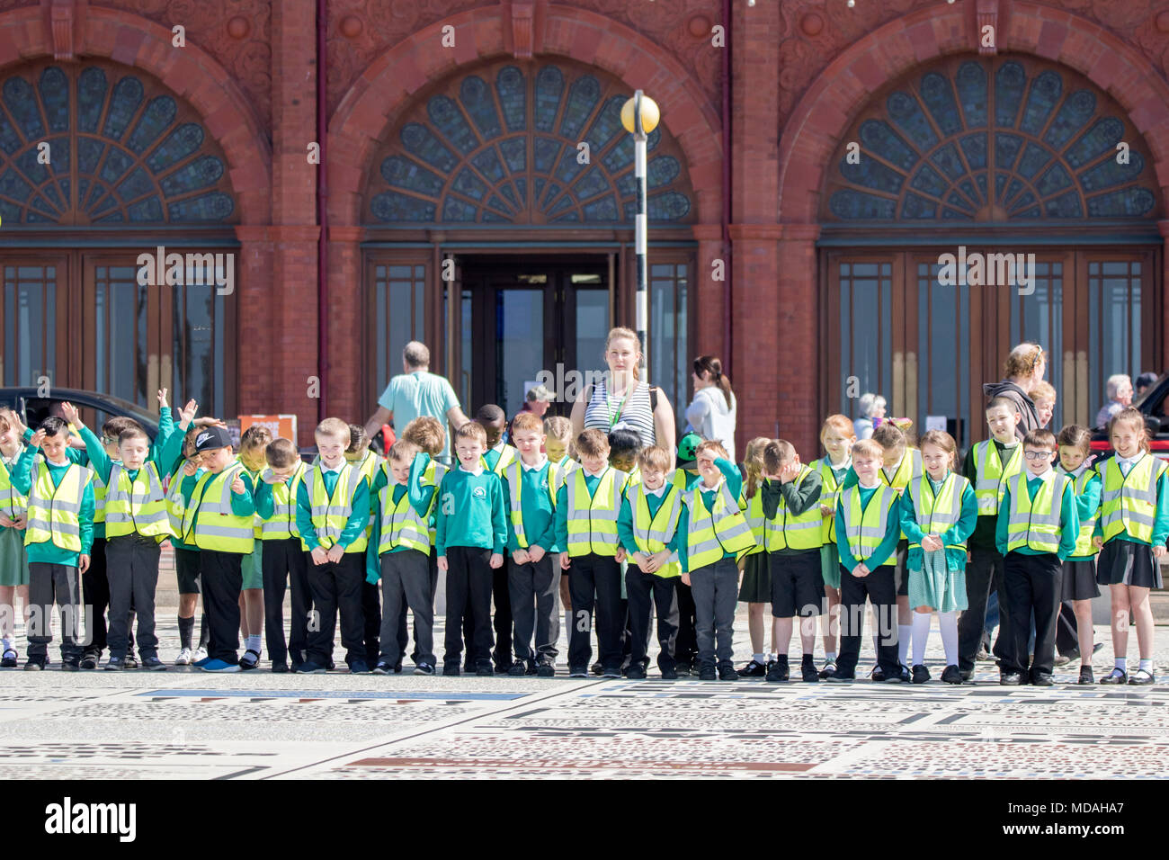 A group of young schoolchildren wearing hi viz vests for a school day outing in Blackpool Lancashire. - Stock Image