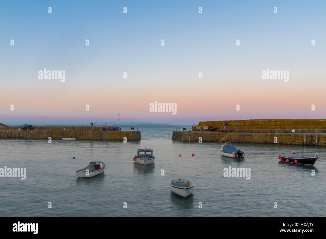 Mousehole, Cornwall, UK. 19th April 2018. UK Weather. The mist and fig didn't lift from the south west of Cornwall until around 3pm today, when it did it was clear skies all the way upto sunset. Credit: Simon Maycock/Alamy Live News - Stock Image