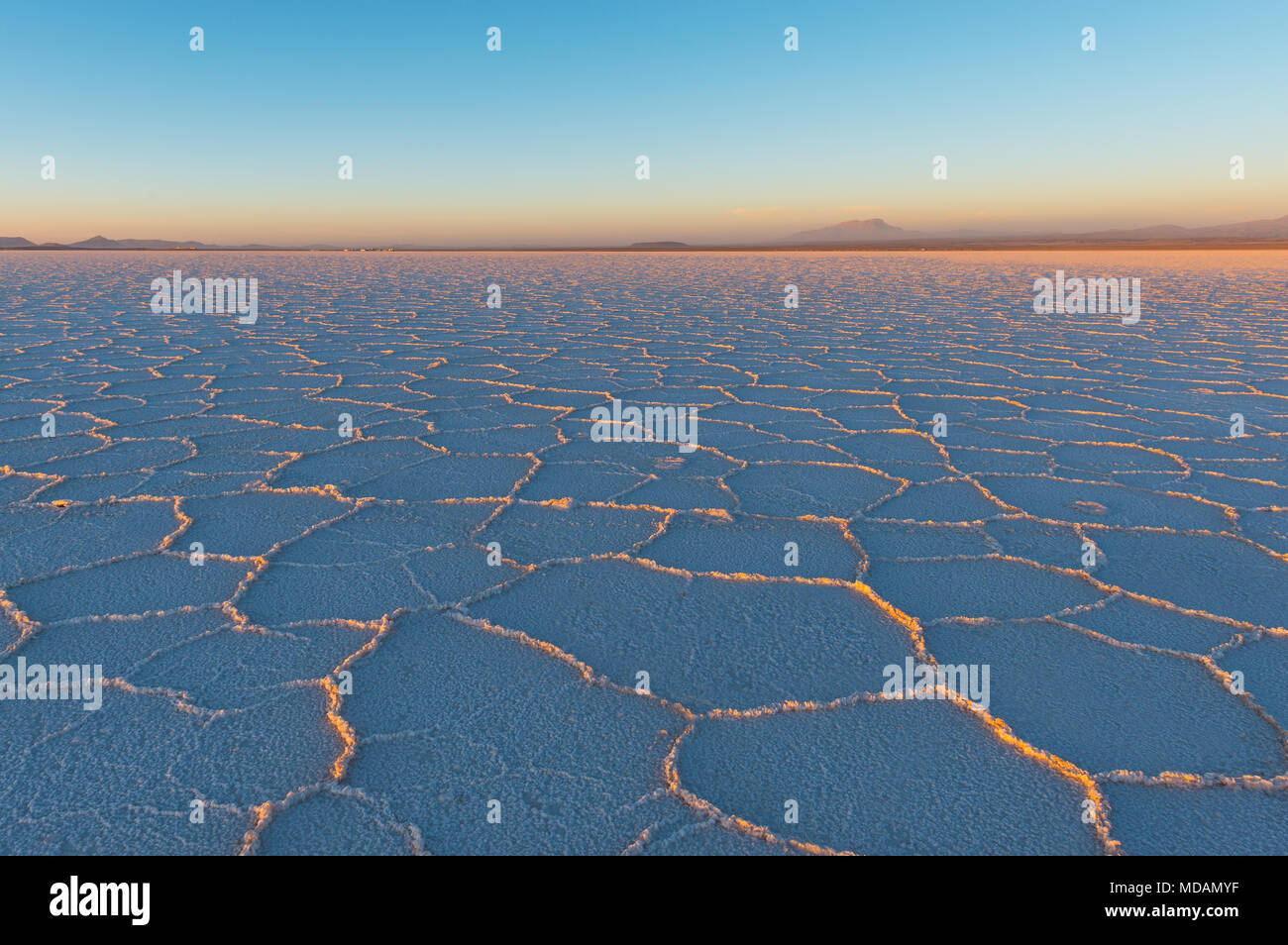 Sunset in the Uyuni salt flat (Salar de Uyuni) with the last sun rays shining on the mineral hexagon formations, Bolivia, South America. - Stock Image