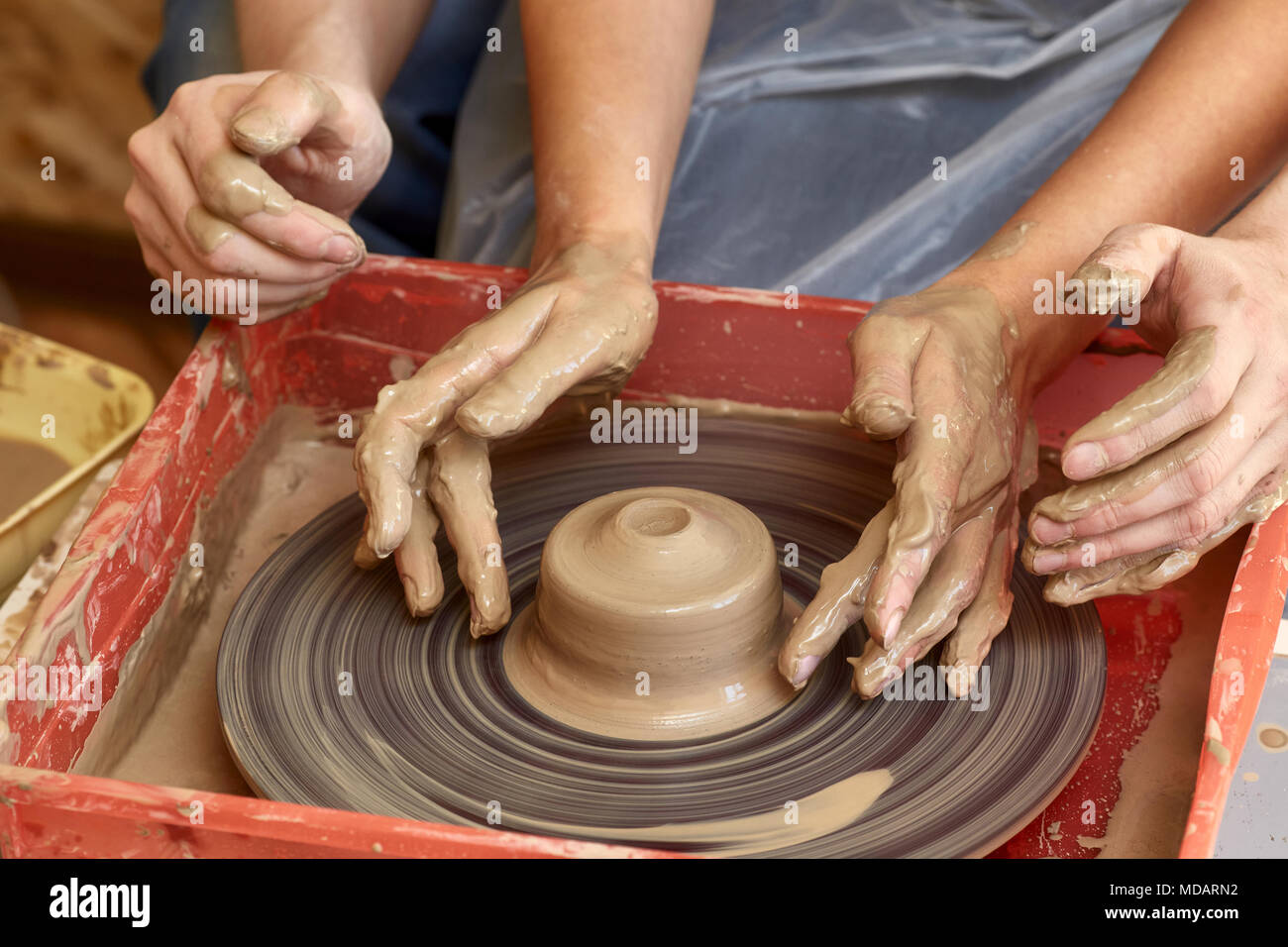 Hands of two people create pot on potter's wheel. Teaching pottery, carftman's hands guiding - Stock Image