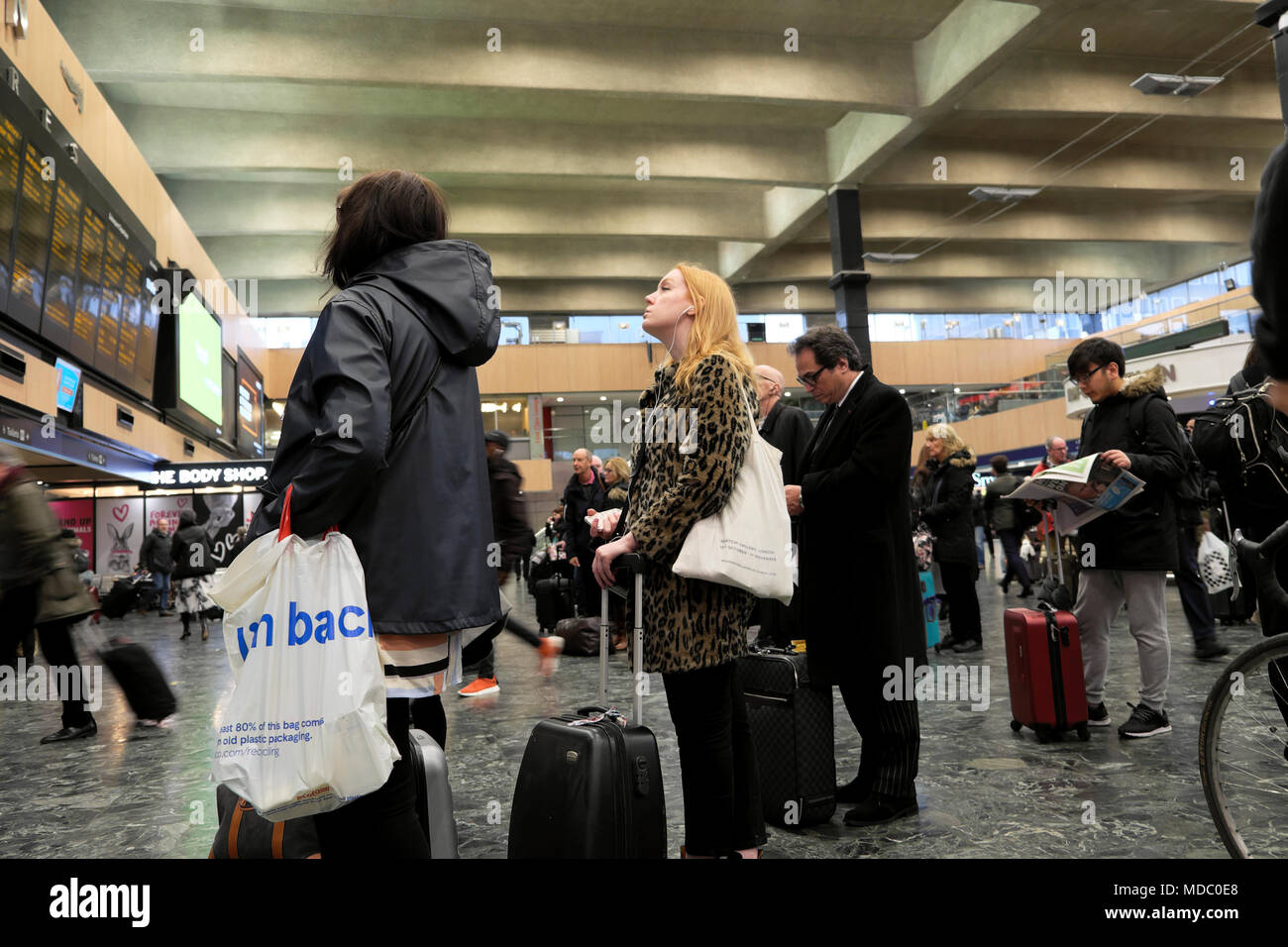 Commuters people standing waiting on the concourse looking at the departure board at Euston Station in London England UK   KATHY DEWITT - Stock Image