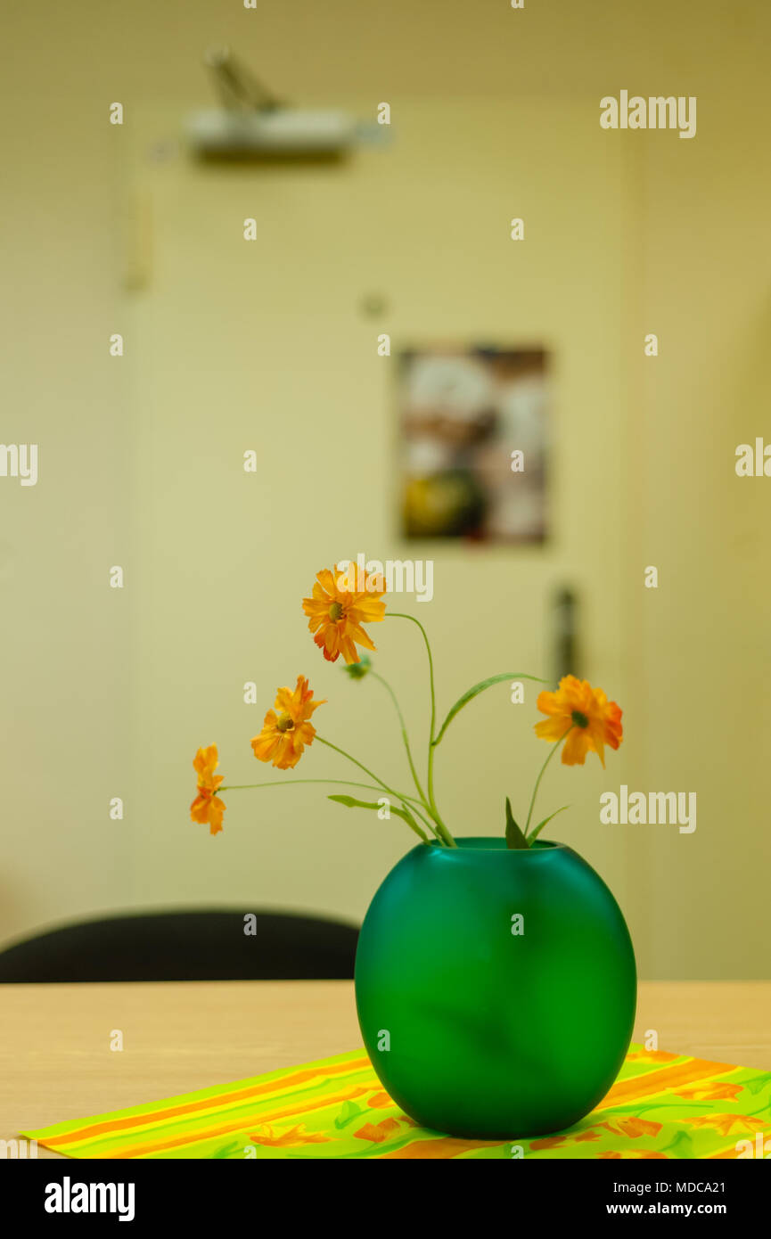 Hamburg, Germany - November 25, 2014: Green vase with synthetic orange  flowers on table in dull restroom. - Stock Image