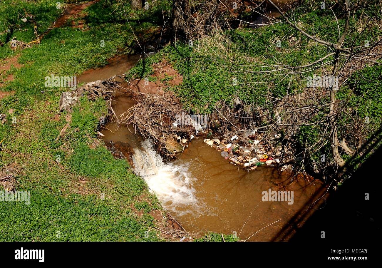 beautiful little river with foliage and plastic bottles and garbage thrown by people, countryside, pollution of nature and water, - Stock Image
