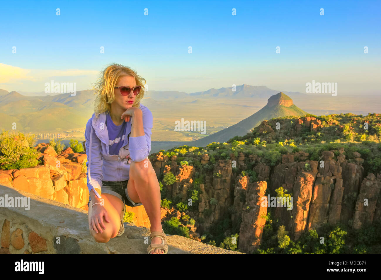 Young tourist sitting on the rocks at sunset after trekking at Valley of Desolation near Graaff-Reinet, South Africa. Blonde woman enjoying aerial views of Camdeboo National Park, Karoo, Eastern Cape. - Stock Image