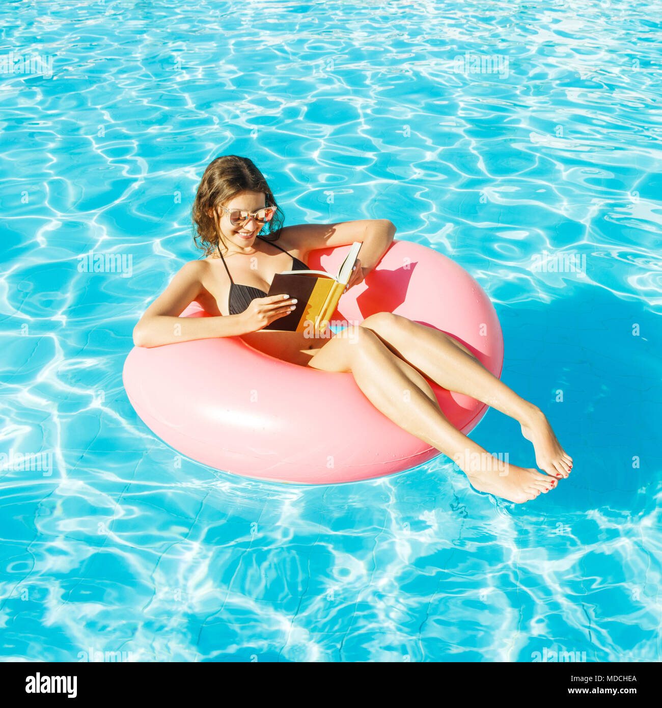 bikini girl with sunglasses relaxed and reading book on pink inflatable pool ring. - Stock Image