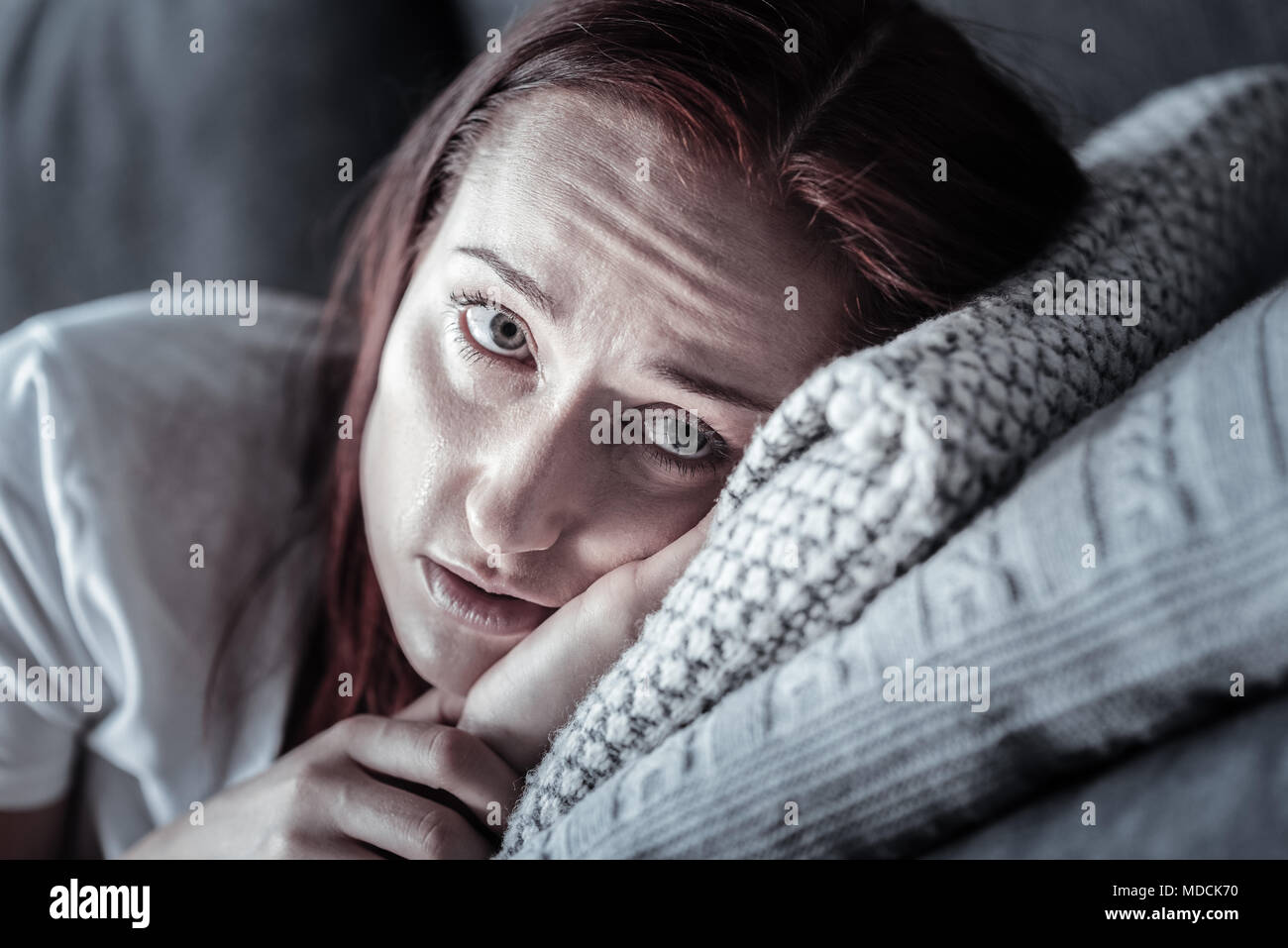 Depressed unhappy woman weeping on pillow - Stock Image