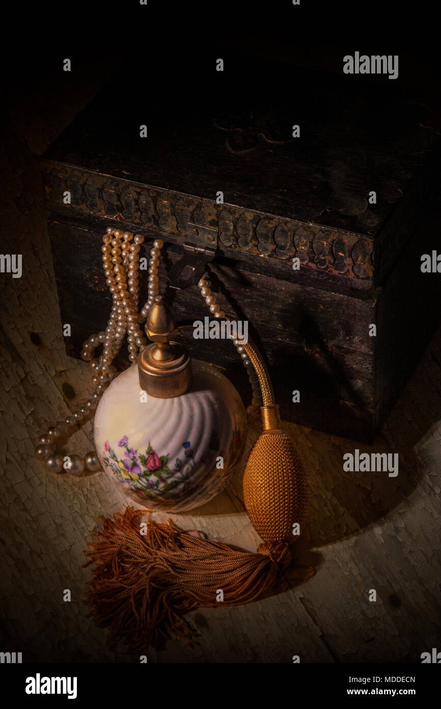 Still life showing perfume atomiser, pearls and wood box - Stock Image