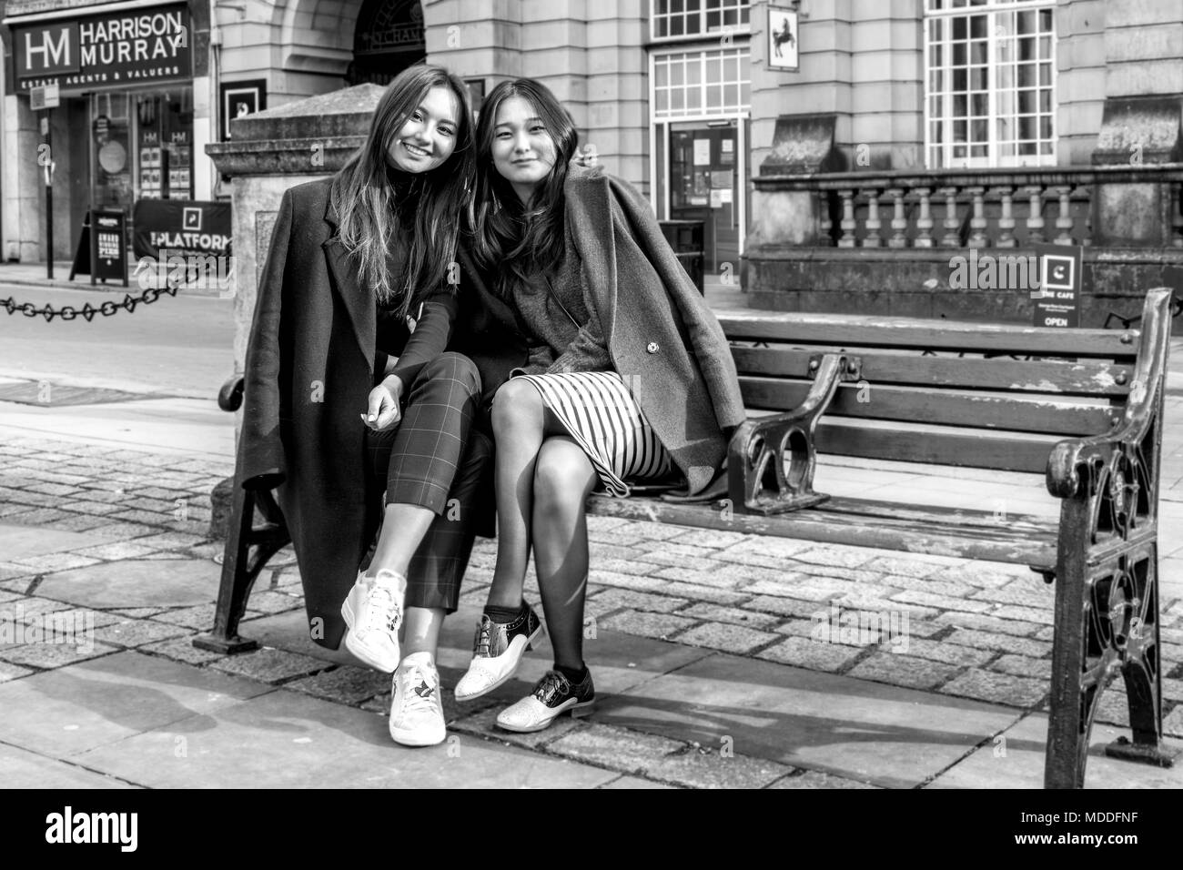 Two Oriental female friends from Northampton college sitting on a wrought Iron and wooden bench at the front of All Saints Church, Northampton town ce - Stock Image