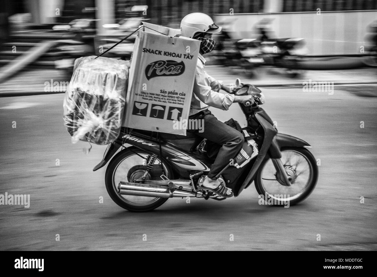 Motion blur motorcyclist carrying products on back of his bike, Hue Vietnam, south east asia - Stock Image