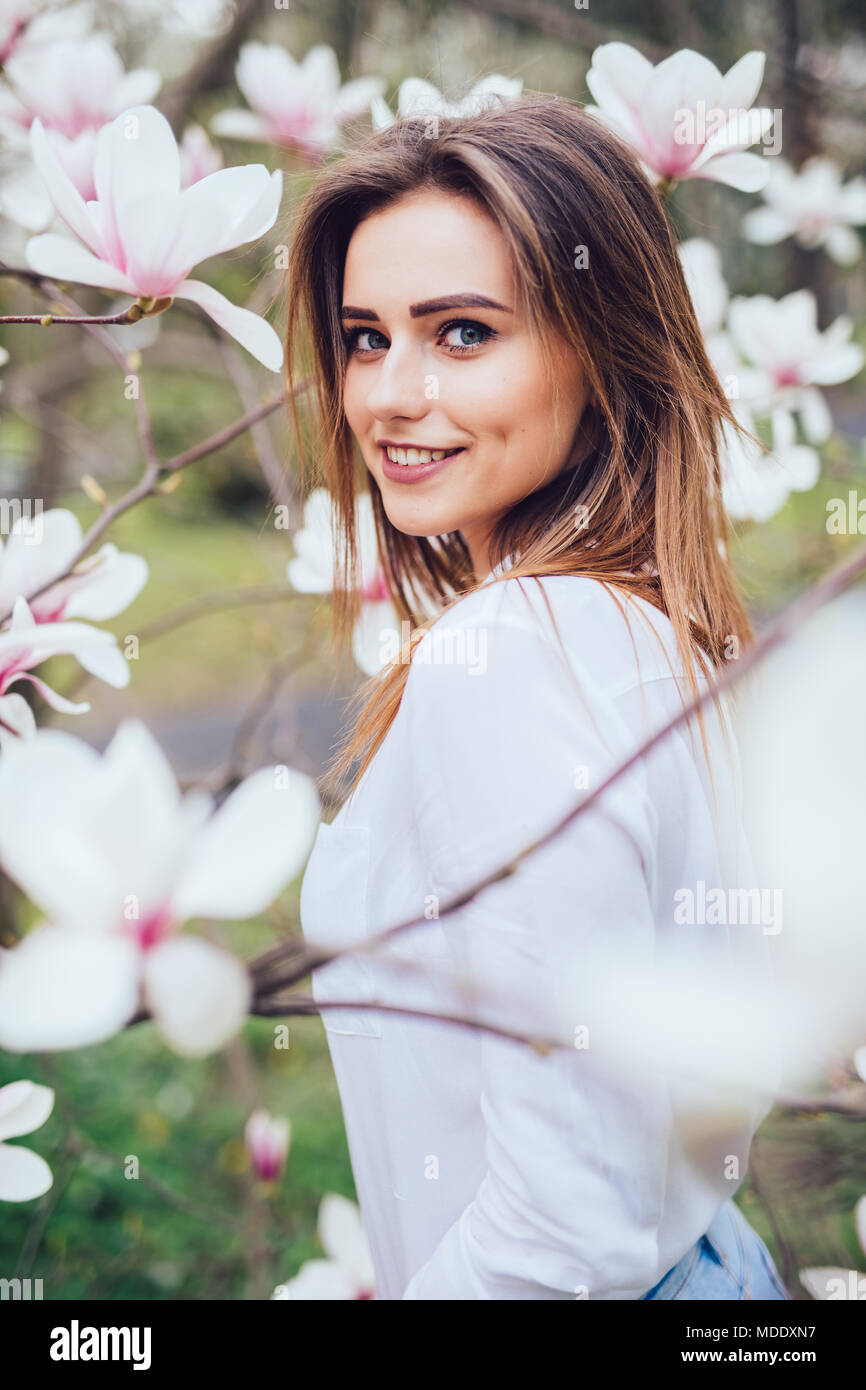 Portrait of young girl near blossom magnolia flowers outdoors in spring park - Stock Image