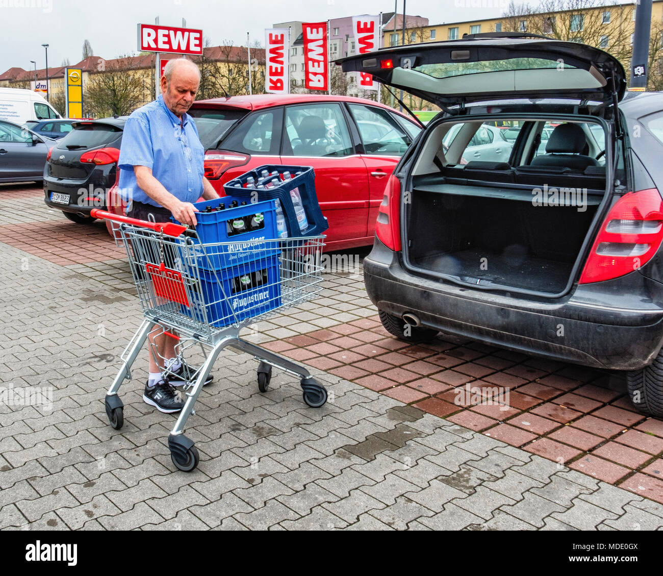 Berlin, Germany. Elderly senior man returning empty bottles to supermarket. Bottle recycling,recycles bottles,pfand deposit system - Stock Image