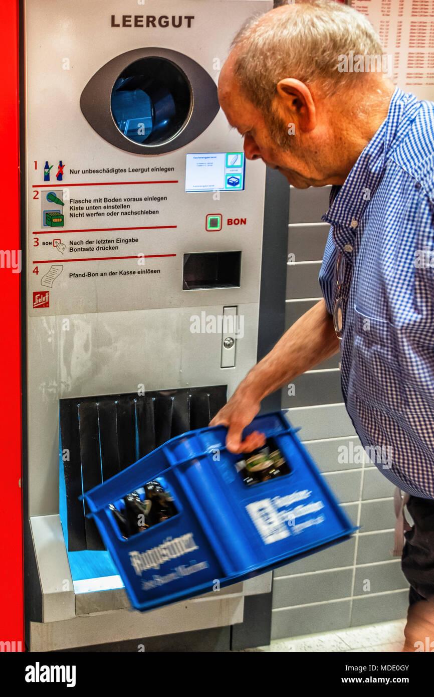 Berlin, Germany. Elderly senior man returning empty bottles to supermarket. Bottle recycling,recycles bottles.pfand deposit system - Stock Image
