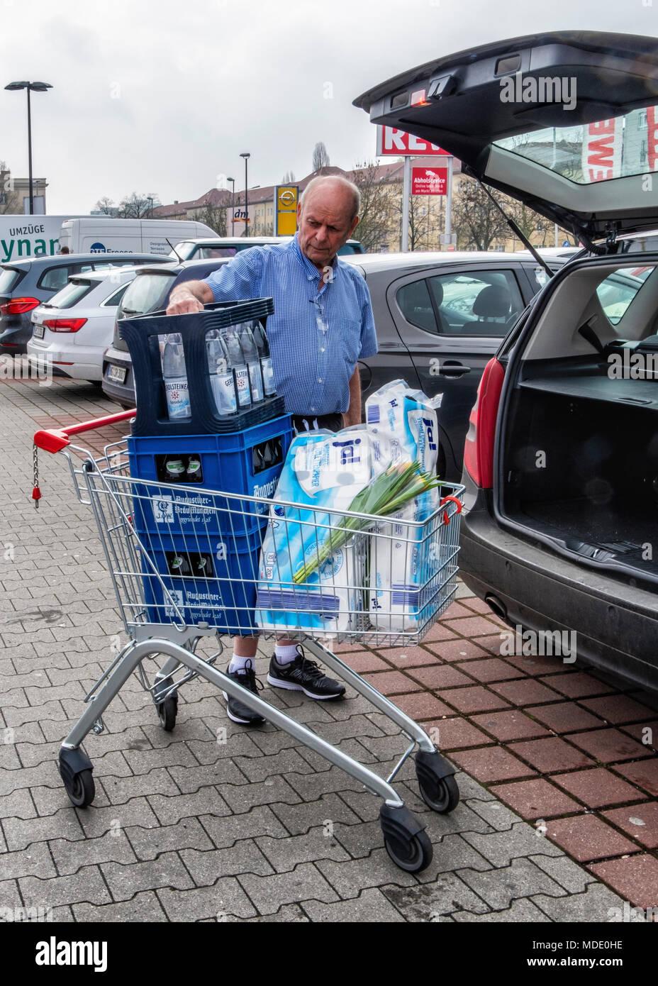 Berlin, Germany. Elderly senior man loading car boot with shopping  at Rewe supermarket - Stock Image