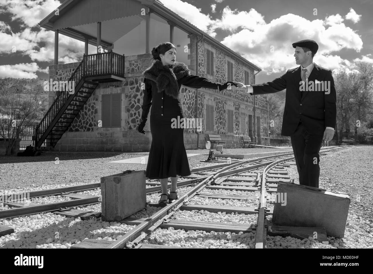 Young couple with vintage suitcase walking on the train lines ready for a journey. - Stock Image