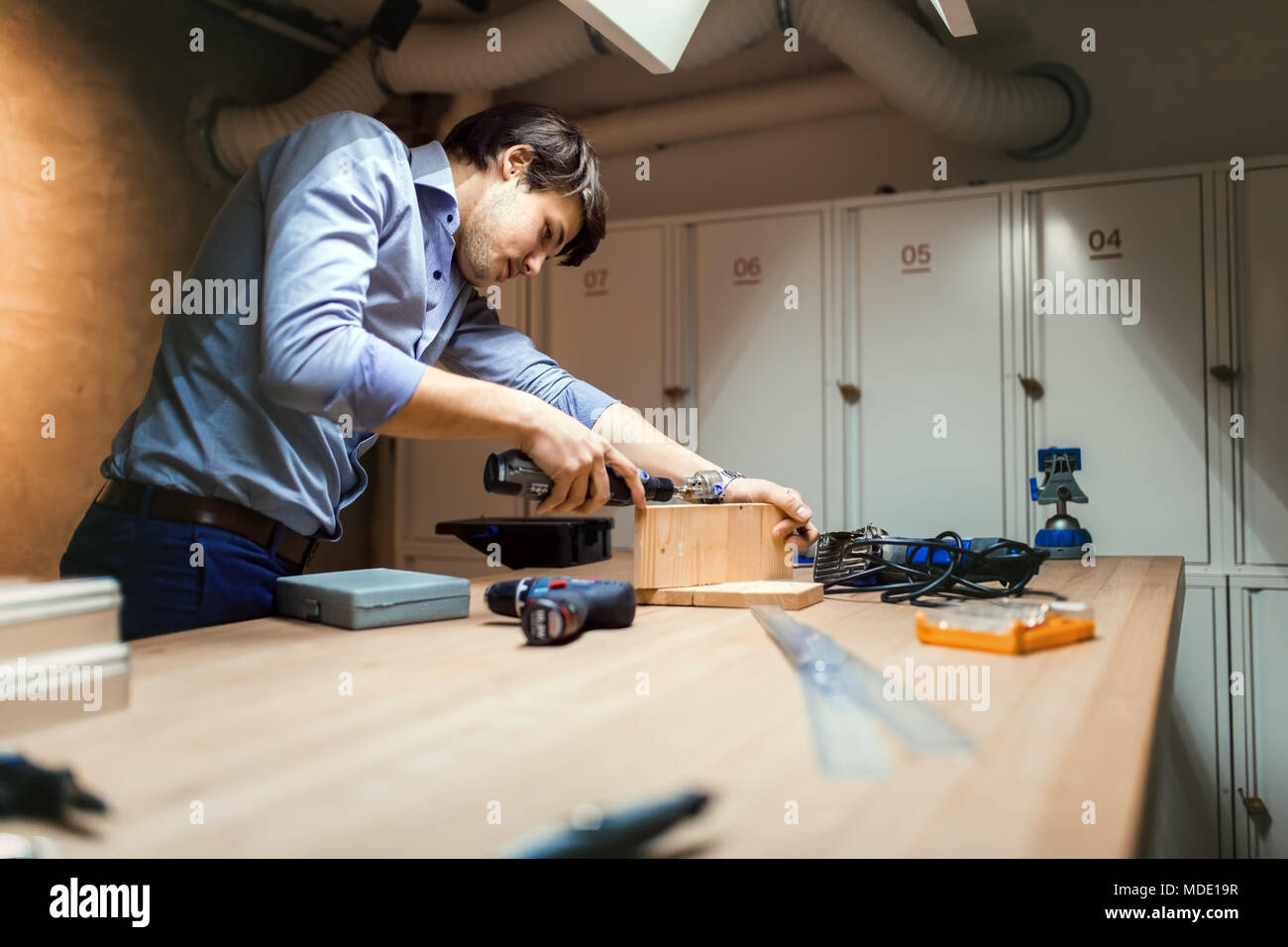 Handyman working with wood - Stock Image