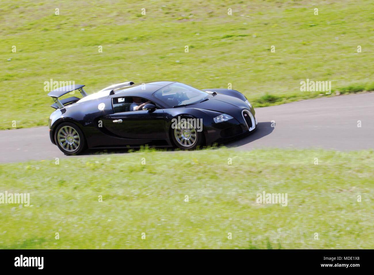 Black Bugatti Veyron Million £ Pound Hyper Car Hypercar Driving Fast On A  Country Road.