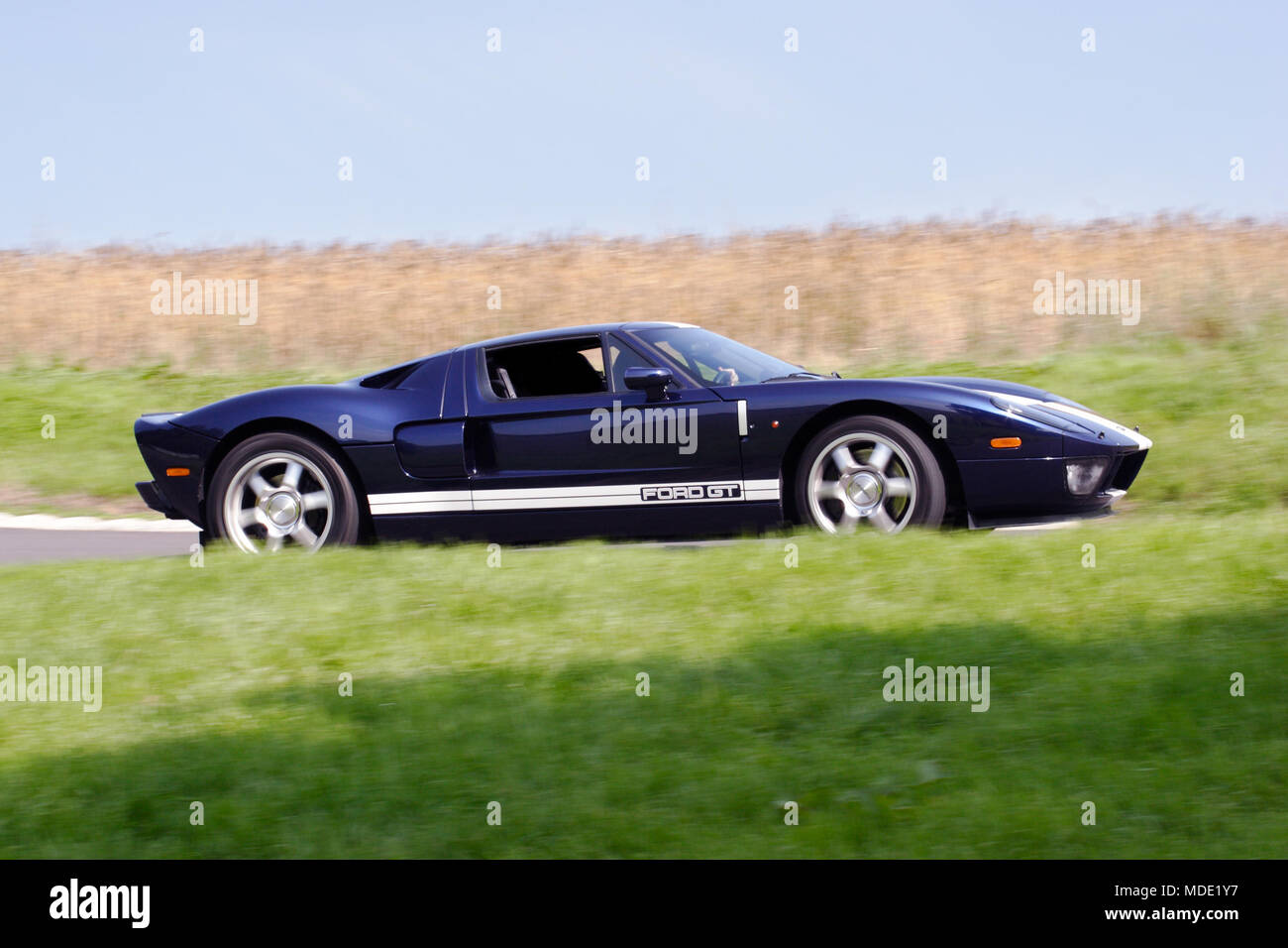 Low Angle Profile Side View Of Navy Blue Ford Gt Supercar Hypercar Driving