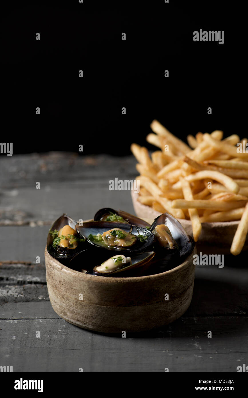 moules-frites, mussels and fries typical of Belgium, on a rustic wooden table, against a black background, with some blank space on top - Stock Image