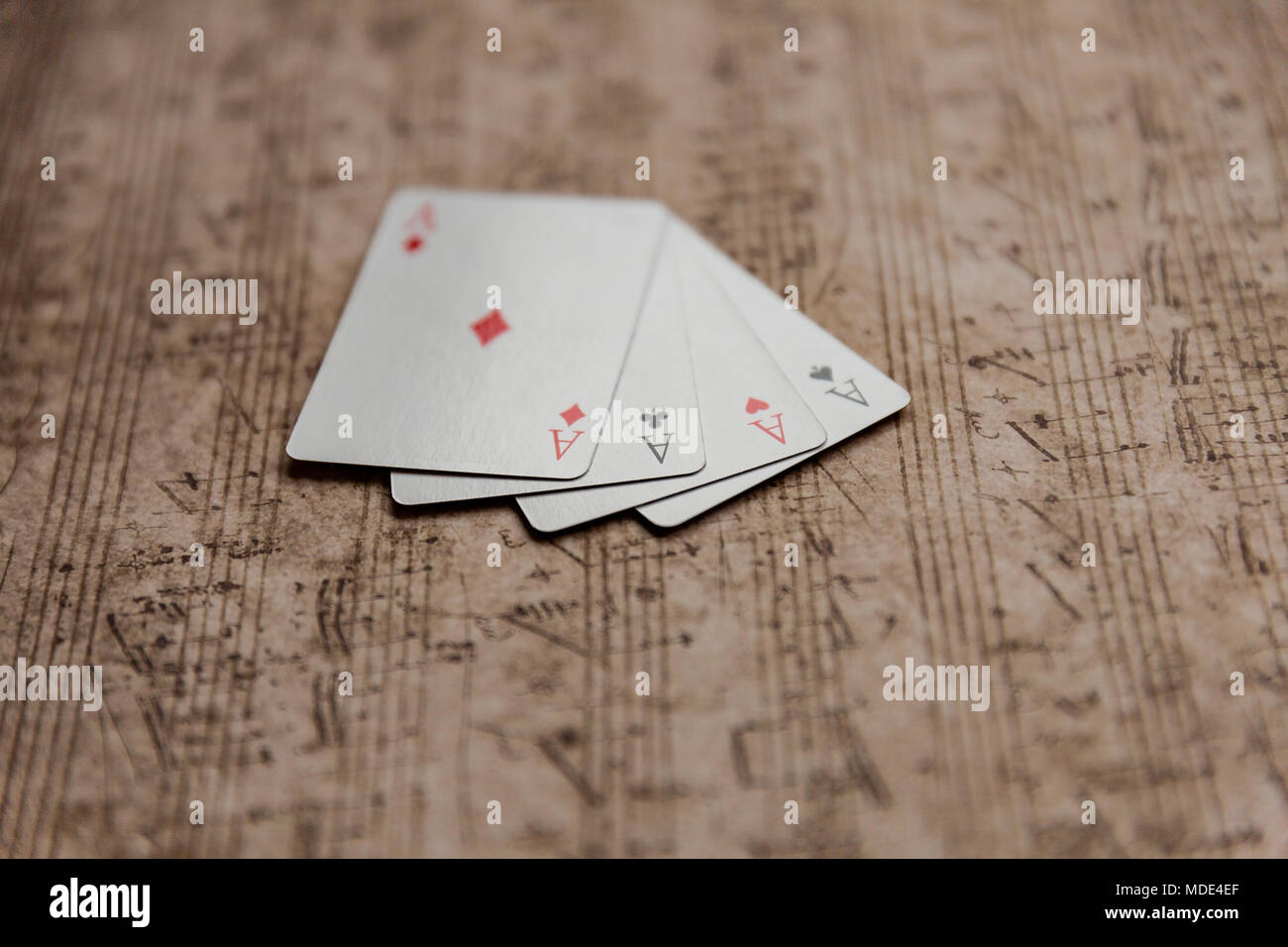 Four aces playing cards on an old musical sheet - Stock Image