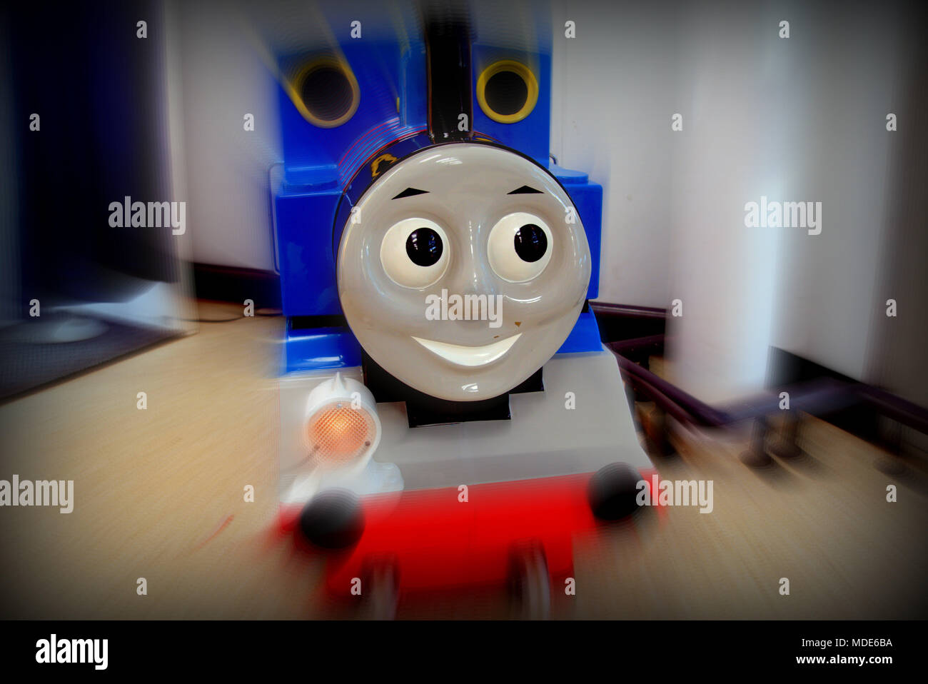 Thomas the tank engine cartoon character as a children's ride with motion blur close up toy  smiling happy face with nobody copy space Stock Photo