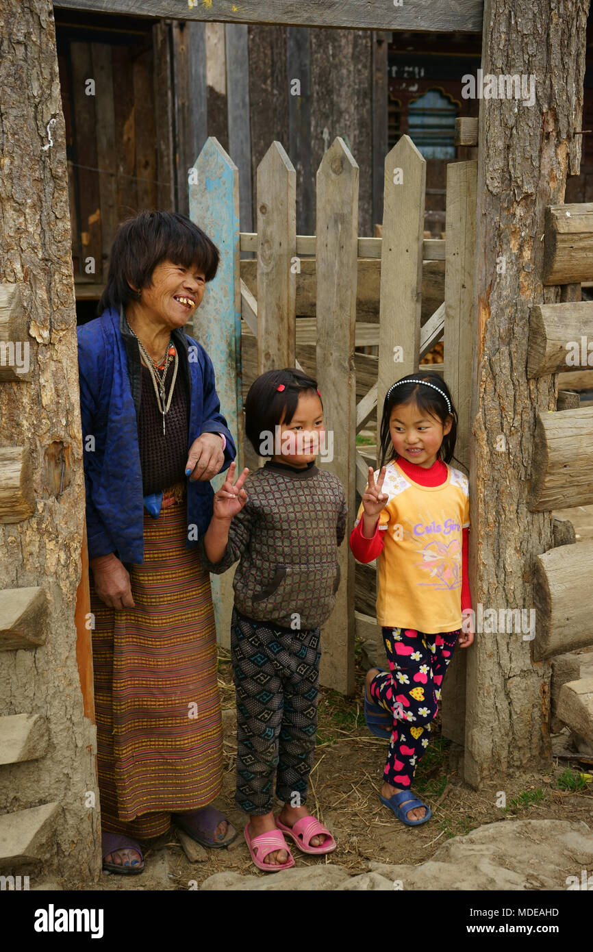 Girls with mother psoe with V-sîgn ibn front of their house at Phobjikha, Bhutan - Stock Image