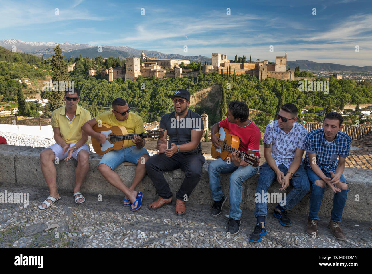 Buskers playing music at the mirador de San Nicolas with the Alhambra and Sierra Nevada mountains behind, Granada, Andalucia, Spain, Europe - Stock Image