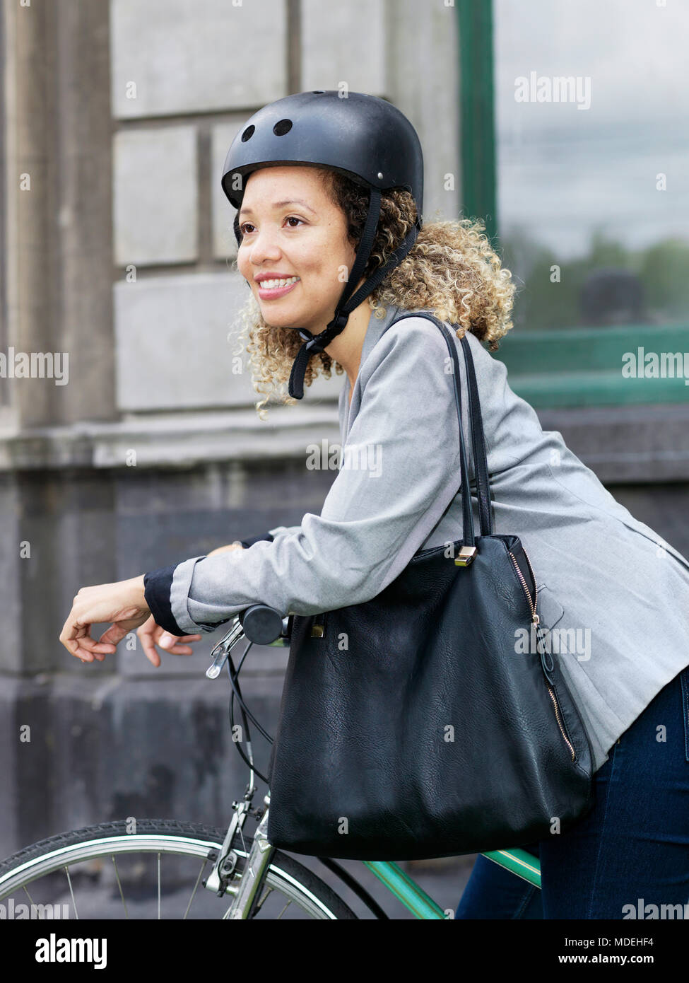 Mid Adult Woman Sitting On Bicycle Wearing Safety Helmet Stock Image