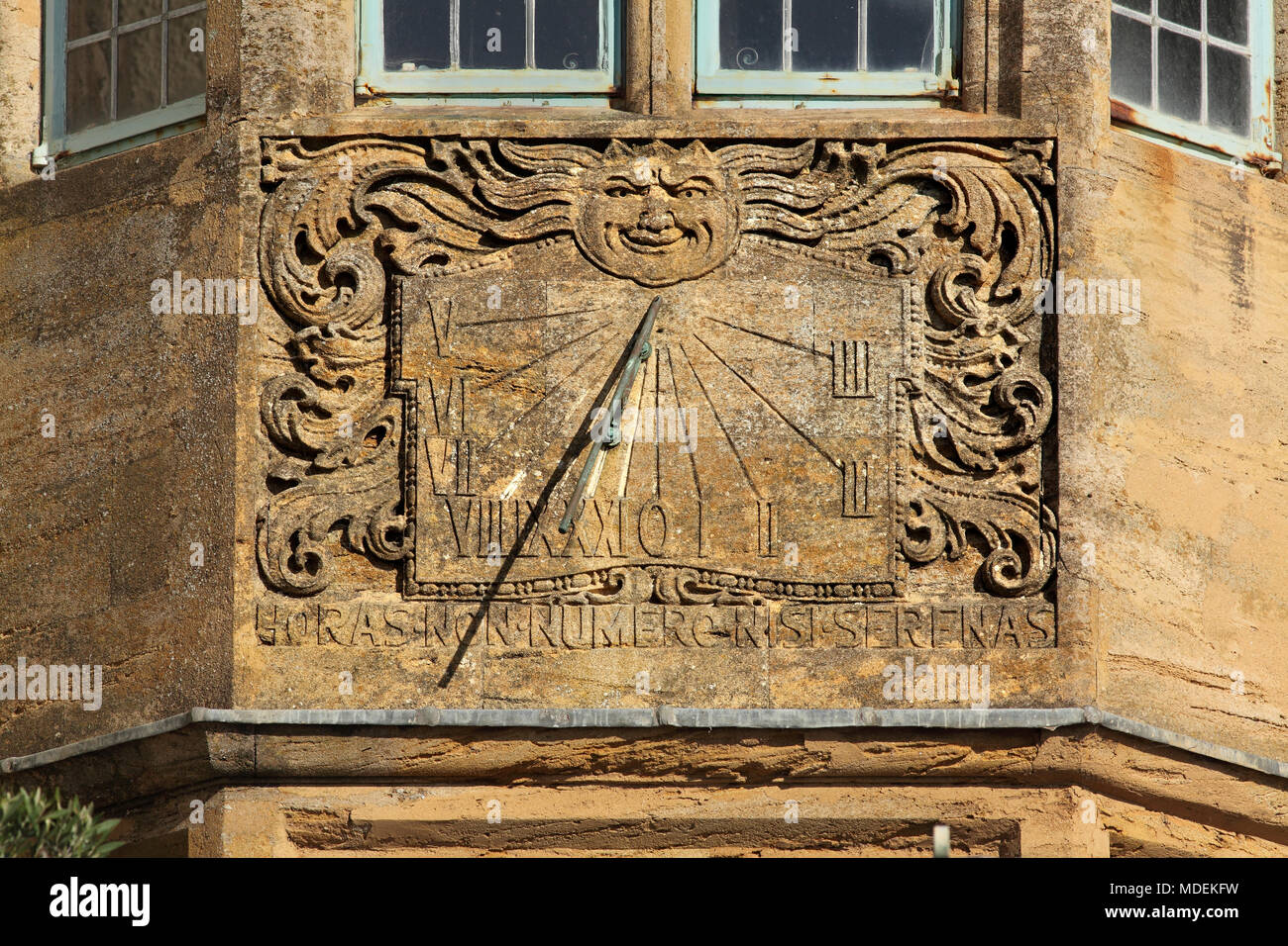 A sundial on a house wall, with Roman numerals, an anthropomorphic image of the sun, and swirling scrollwork, Lyme Regis, Dorset. - Stock Image