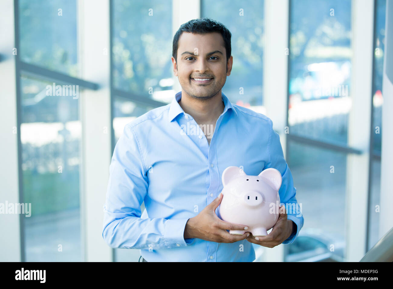 Closeup portrait happy, smiling businessman, holding pink piggy bank, isolated indoors office background. Financial budget savings, smart investment c - Stock Image