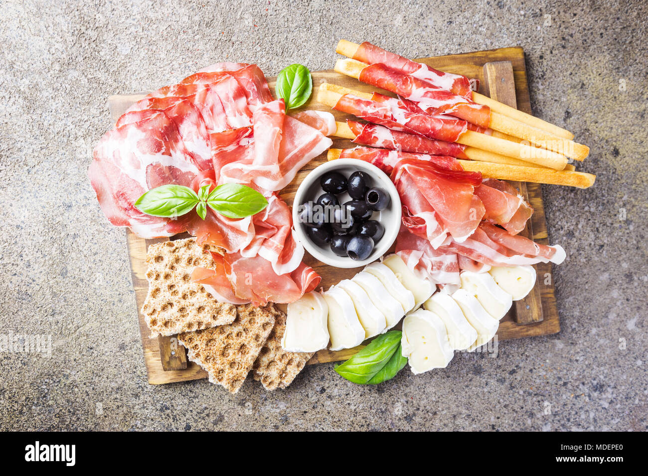 Cold meat plate with cheese olives and bread on cutting board over gray stone background & Cold meat plate with cheese olives and bread on cutting board over ...