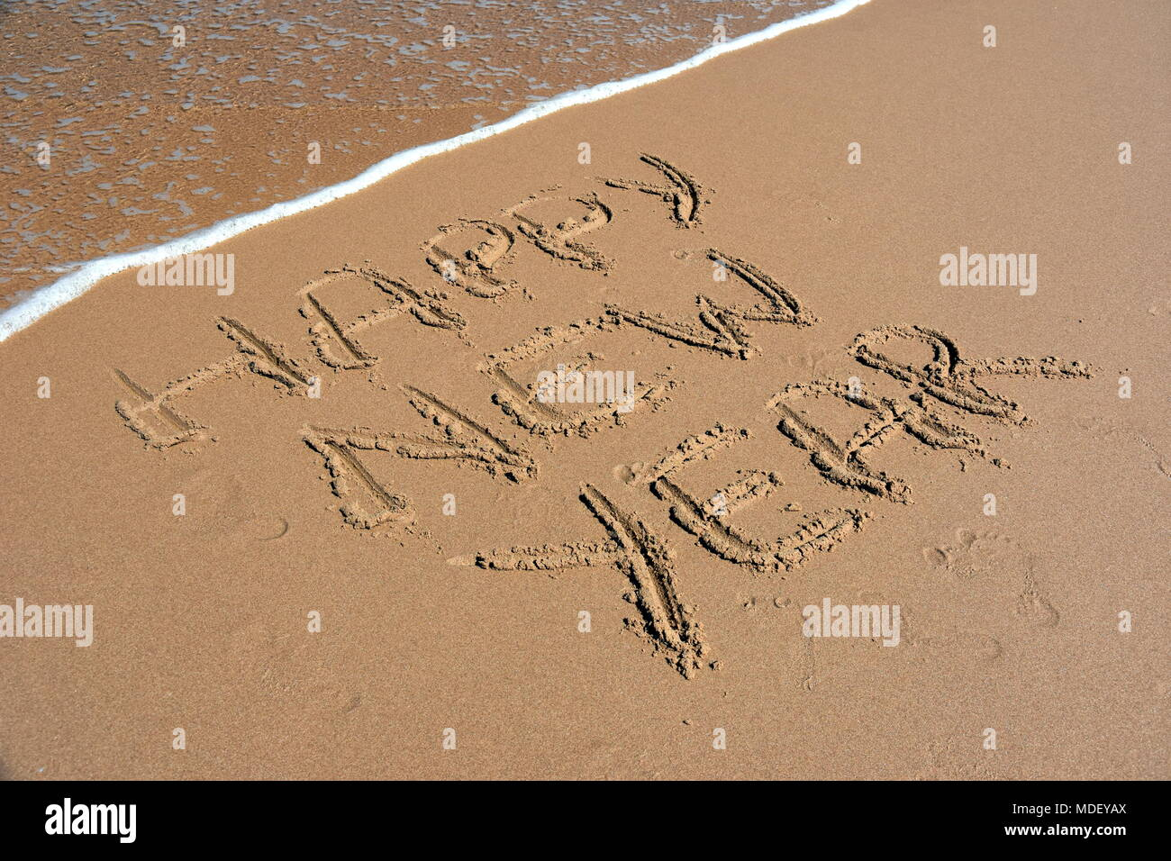 happy new year written on sand at sunset happy new year lettering on the beach happy new year drawn on sand on a beach closeup shot happy new yea