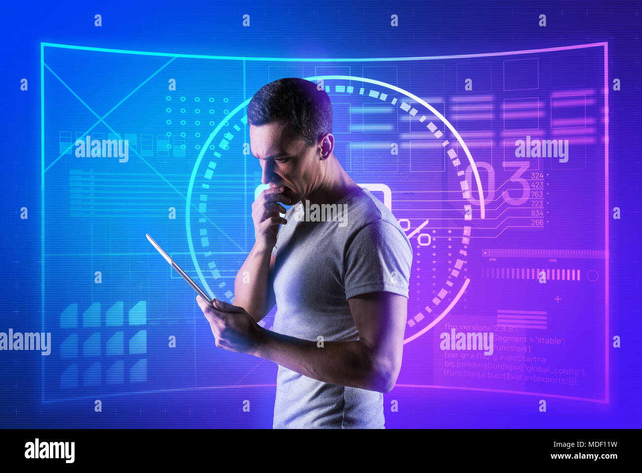 Serious software engineer thinking while standing with a modern tablet - Stock Image