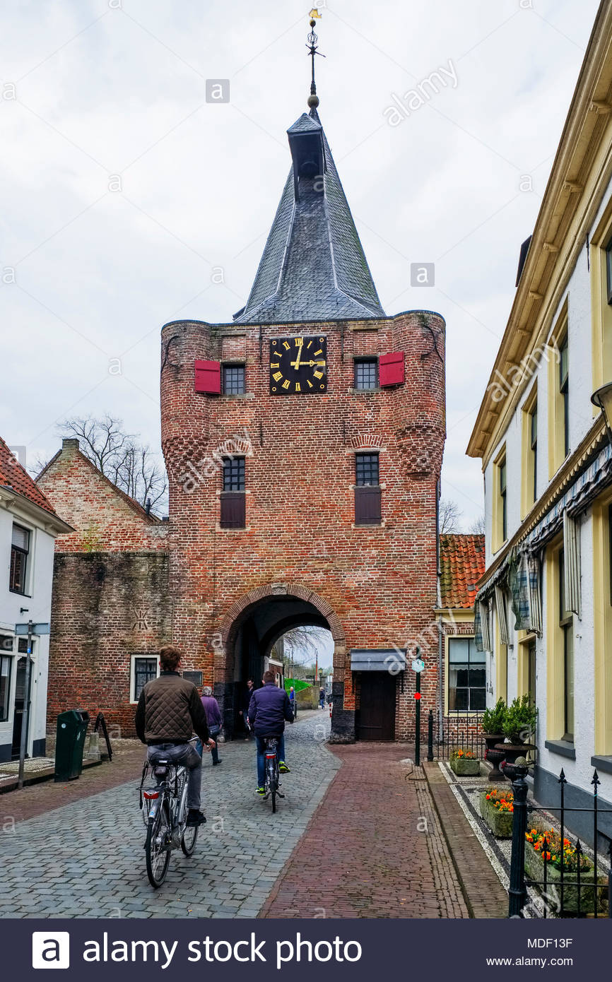 People stroll and bike through the Vischpoort, a defensive tower built in the early 15th century; the passageway added in 1592 leads to Elburg harbor. Stock Photo