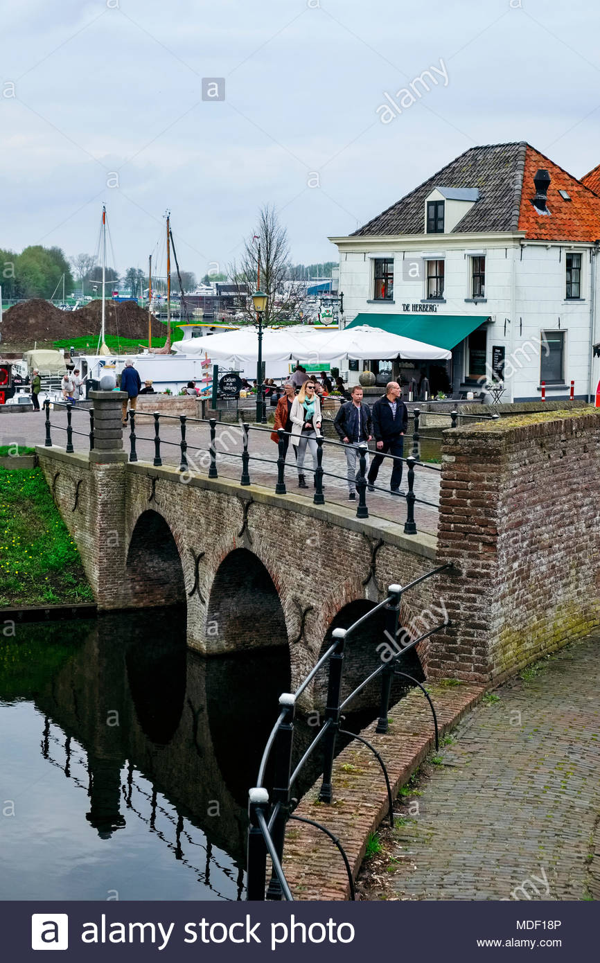 People cross the bridge on Havenstraat that leads to the old fortress city of Elburg as others enjoy lunch at De Herberg restaurant beside the harbor. - Stock Image