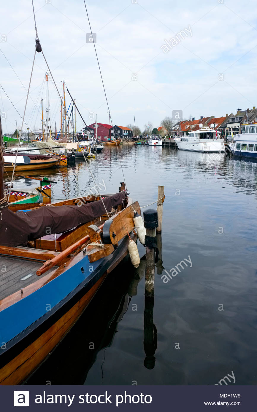 Classic wooden boats and other watercraft are moored in the harbor of the small city of Elburg, in the Netherlands. - Stock Image