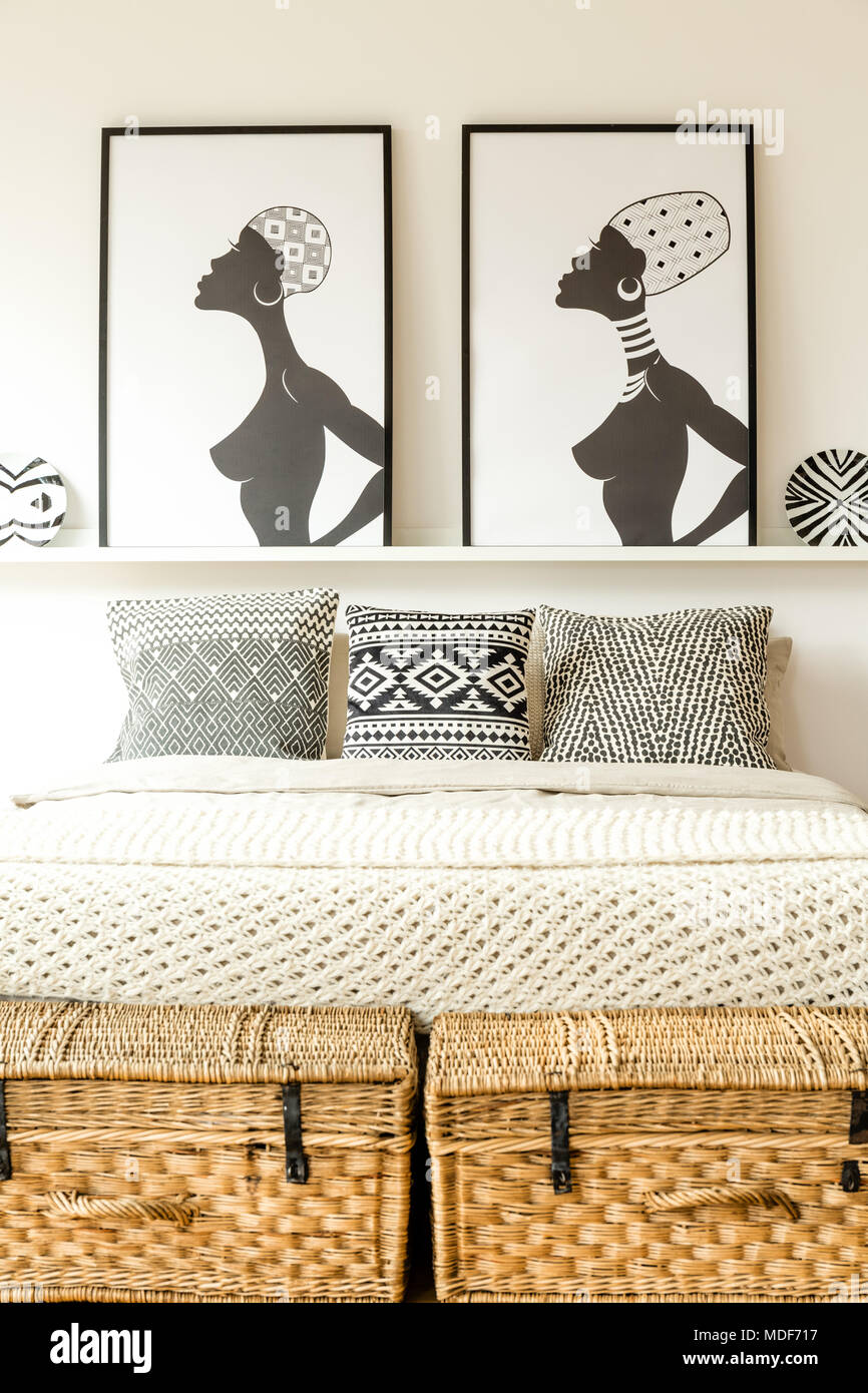 Front view of a comfy double bed, wicker boxes and posters with African women in bedroom interior - Stock Image