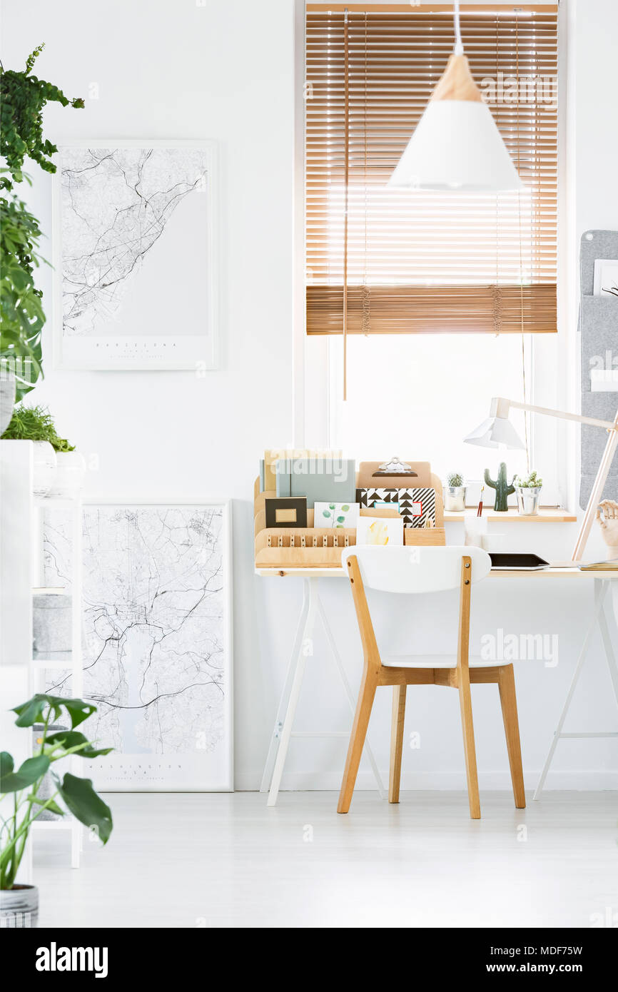 Wooden desk organizer, blinds, white wall and chair in modern home ...